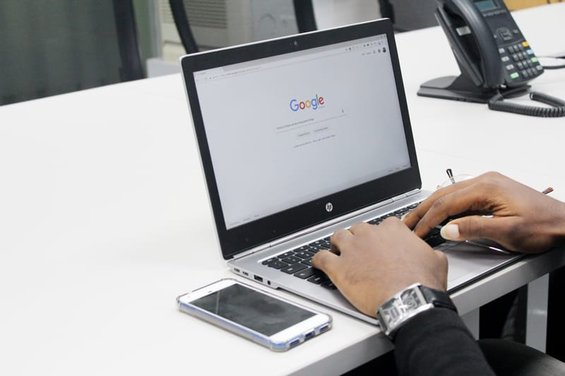 A man types on a laptop computer, currently open to the Google search bar home page.