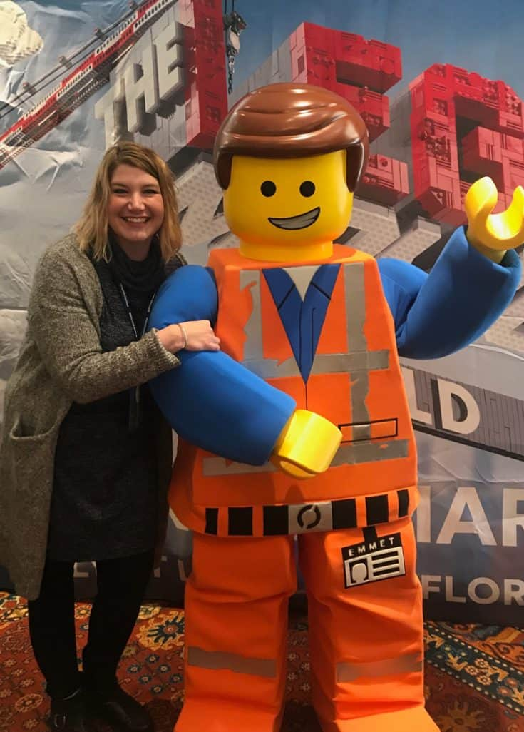 Jenny standing beside a life-size replica of Emmet, the main character of The Lego Movie.