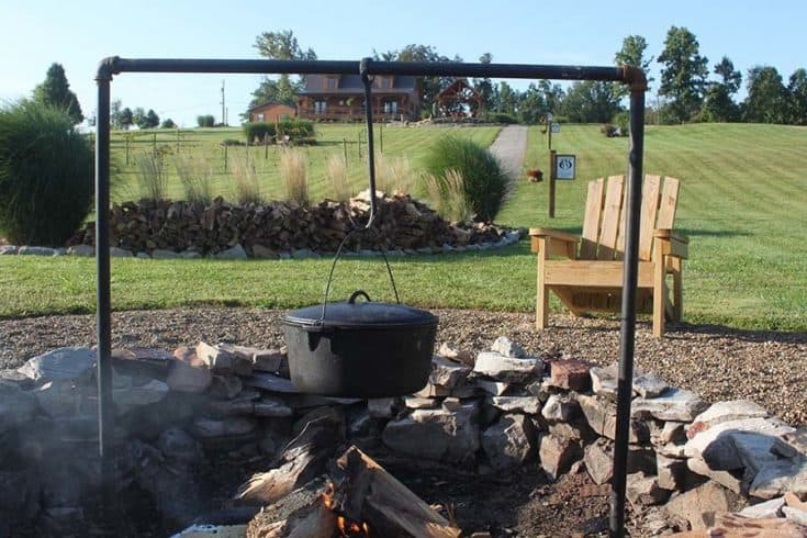 A cooking plot over a campfire, and a lawn chair.