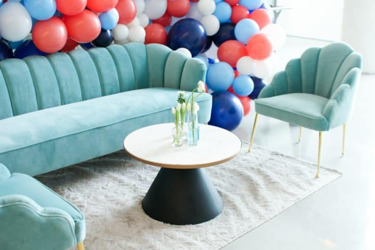 A seating area set up with two chairs, a couch, and coffee table, framed with a balloon arch.