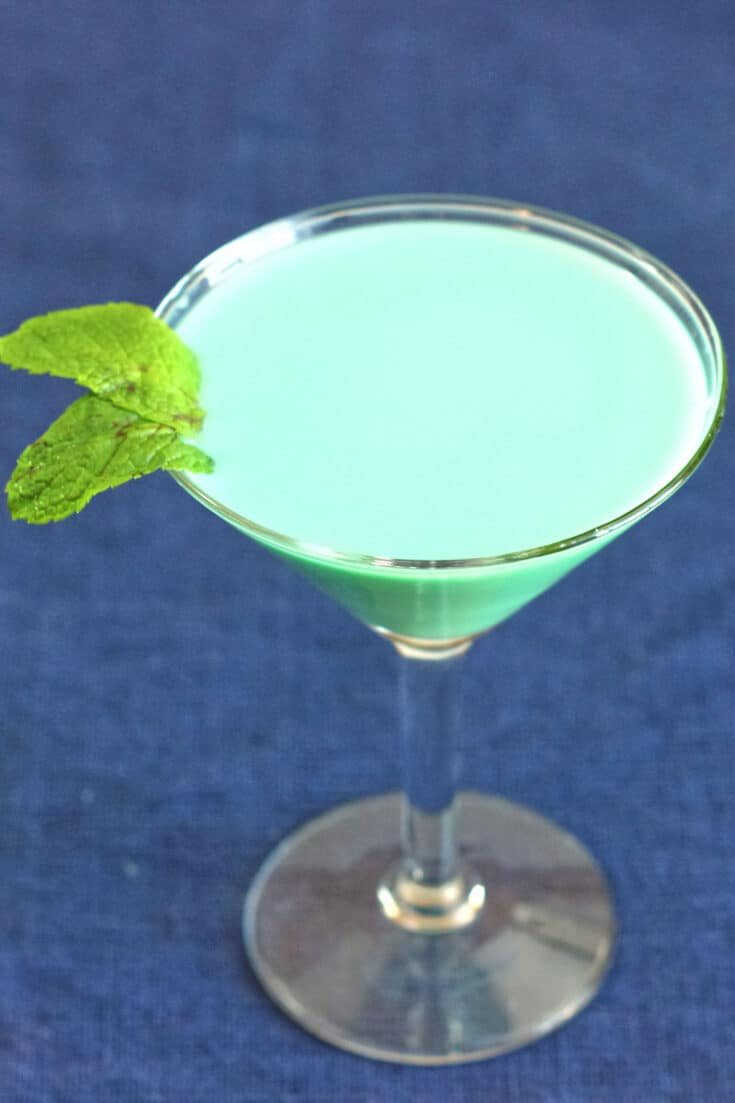 A mint green opaque cocktail, garnished with mint leaves.