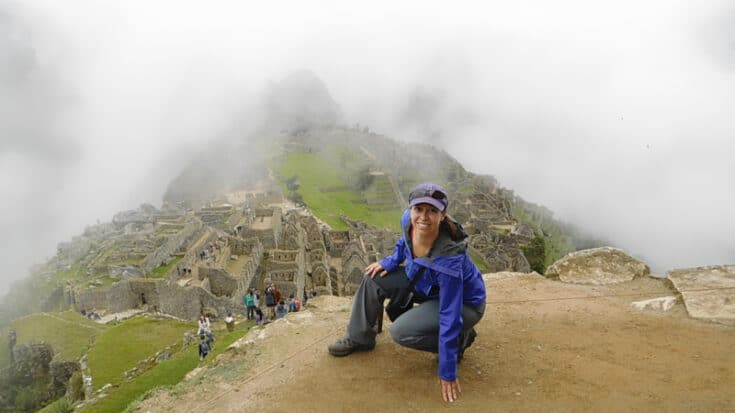 Cynthia kneeling in front of the misty ruins of Machu Picchu.