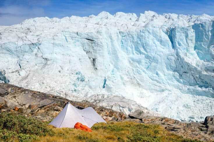 A tent set up on the mountains, overlooking a glacier.