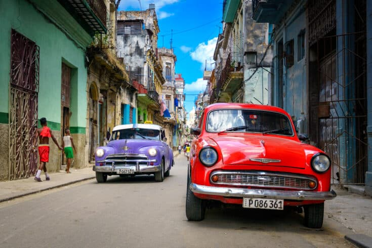 Colorful classic cars in a narrow road.