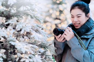 Woman holding a camera next to a fake snowy christmas tree