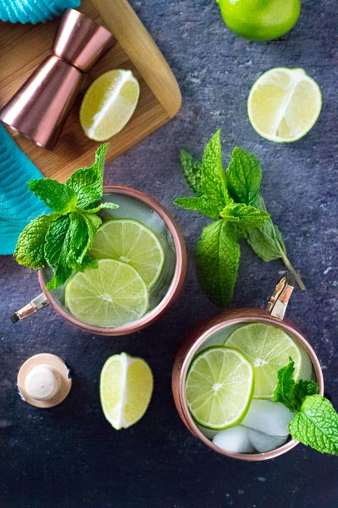 Gin moscow mules in copper tumblers, garnished with lime and mint.