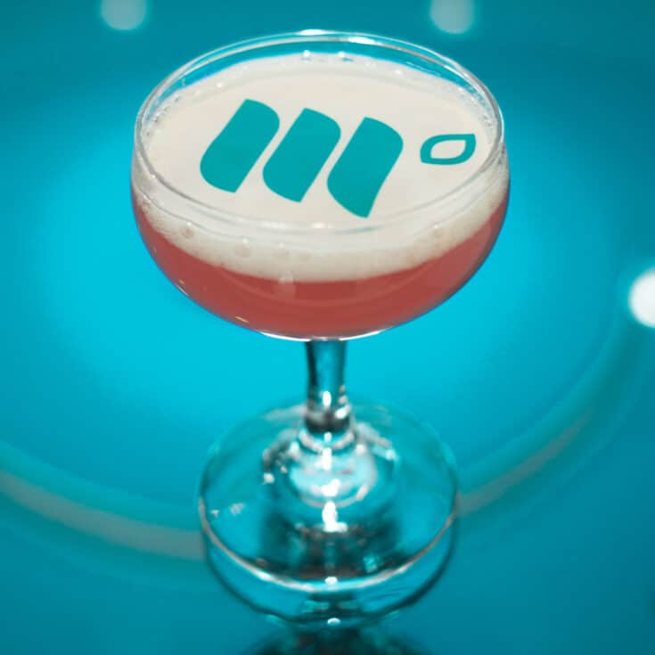 A cocktail with the Mediavine logo on top of the fizz in edible paper.