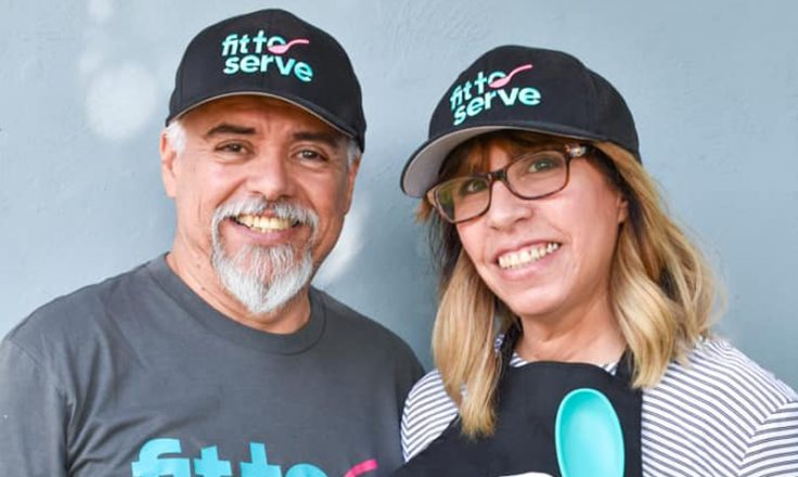 Hilda and partner wearing fit to serve shirts and hats