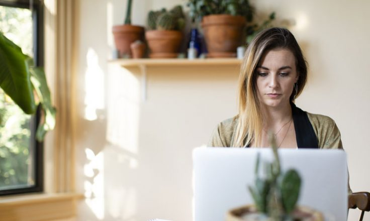 woman looking at computer in her office