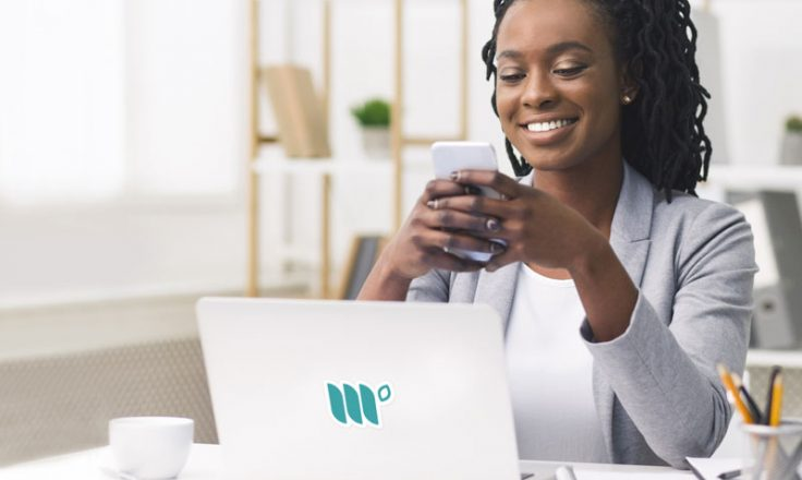 woman using phone sitting next to laptop at a desk