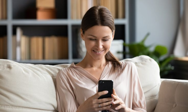woman sitting on couch in home smiling at phone
