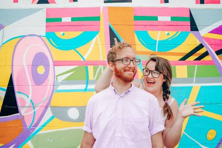 Lia Garcia and her husband stand in front of a colorful mural.