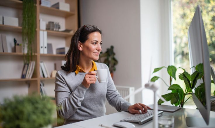woman holding mug while typing with one hand smiling at computer screen