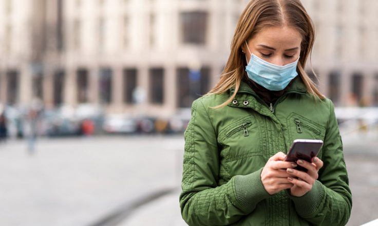 woman in a green jacket wearing a mask and looking at her phone on a city street