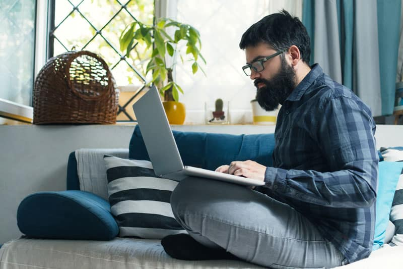 man typing on a laptop in his lap while sitting on a gray couch near a window