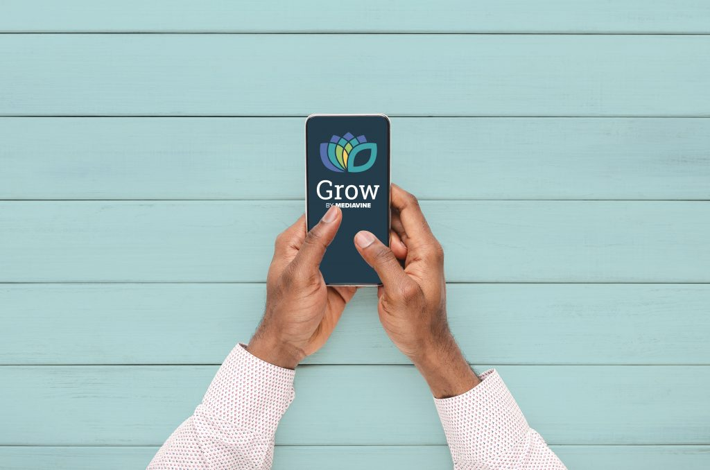 male hands using a phone displaying the grow by mediavine logo on a blue background