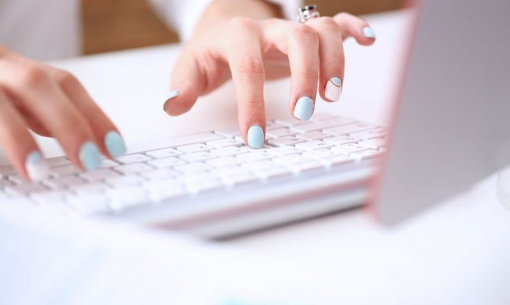 close-up of woman typing on laptop