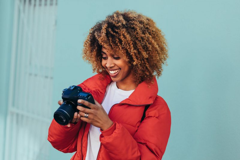 woman in red puffy jacket looking at photos on a DSLR camera in front of a blue building