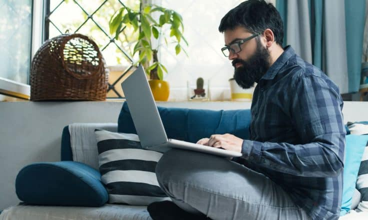 male developer wearing plaid shirt coding on a laptop from a couch