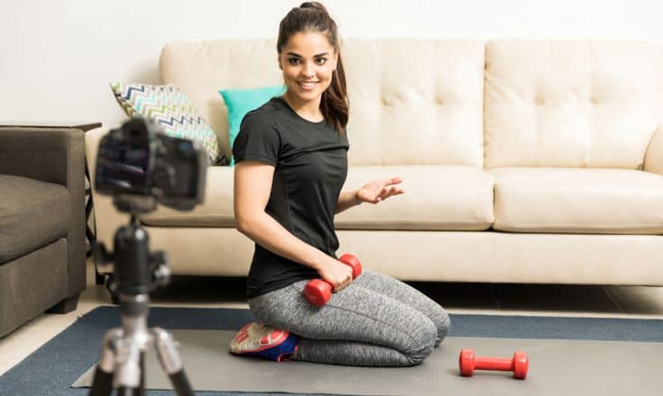 female fitness blogger filming an exercise video on a yoga mat in her living room