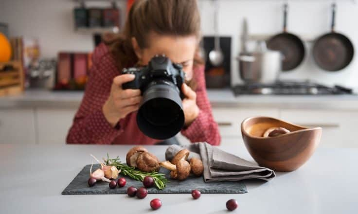 female food blogger photographing fresh produce on a gray napkin in her kitchen