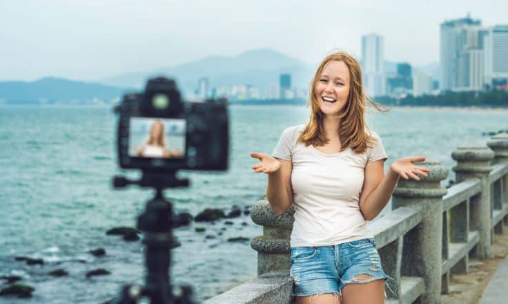 female travel blogger filming a travel video on a bridge with skyline behind her