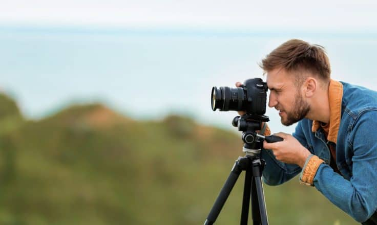 male travel blogger taking photos on a DSLR camera on a tripod with cliffs and ocean behind him