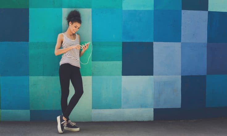 woman wearing headphones leaning against a colorful mural while looking at her phone