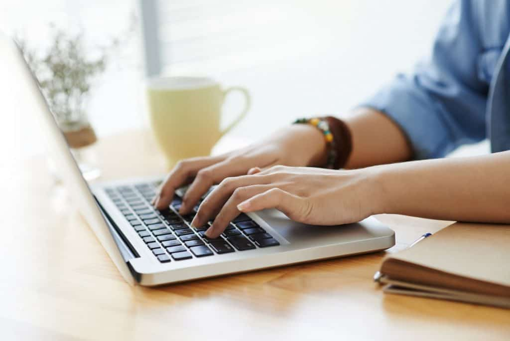 hands typing on a laptop computer on a wooden desk next to a cup of tea