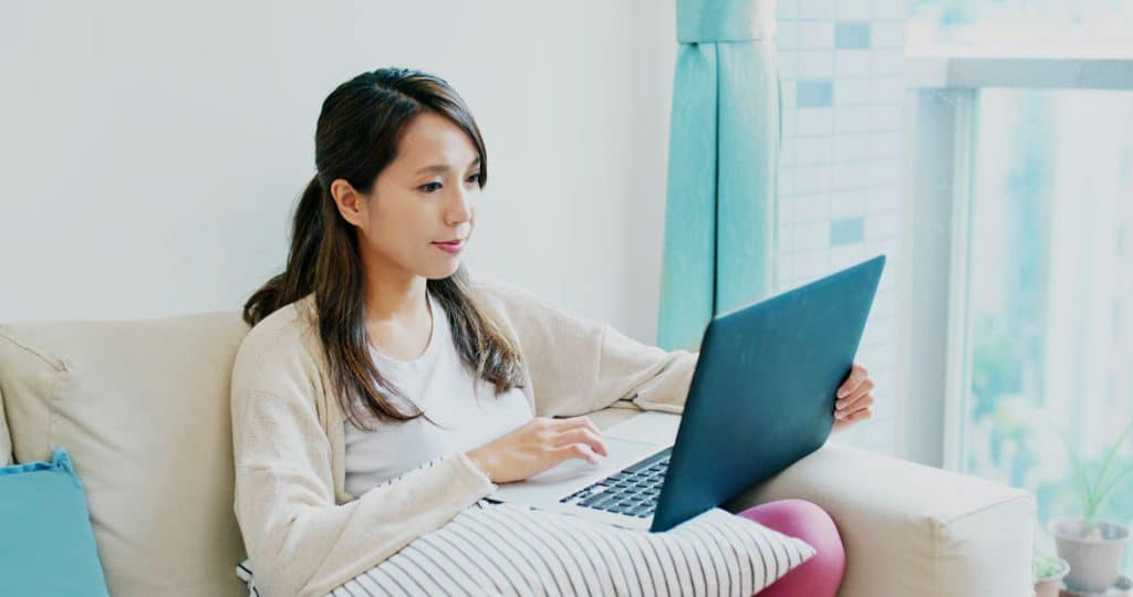 young woman working on her website from a laptop on her couch in her home