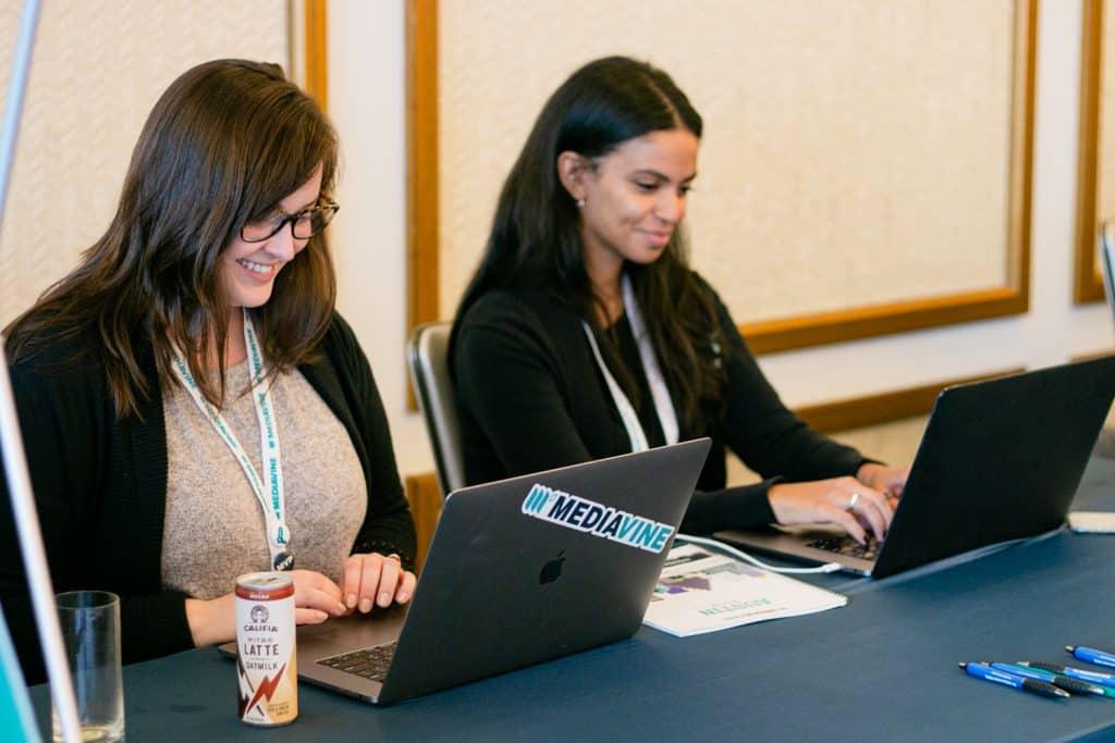 two mediavine team members typing on their laptops
