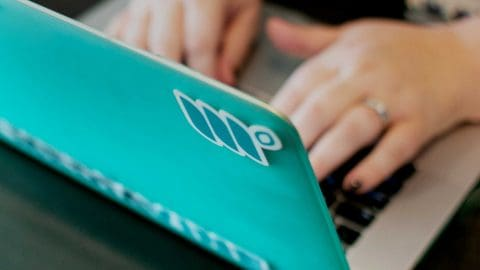 woman's hands typing on a teal computer covered in Mediavine stickers