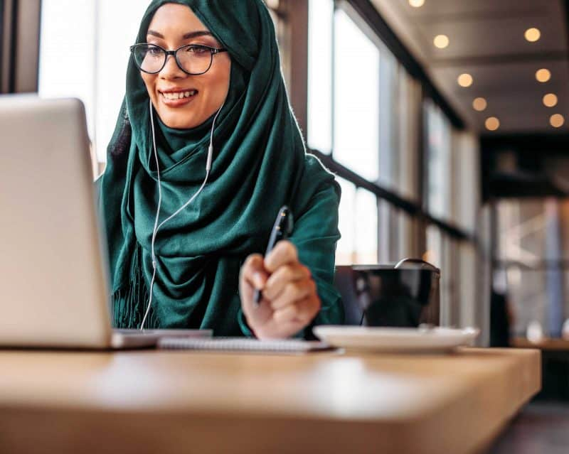 woman wearing headscarf blogging in a cafe