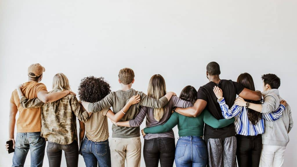 photo of people of multiple races with their arms around each other