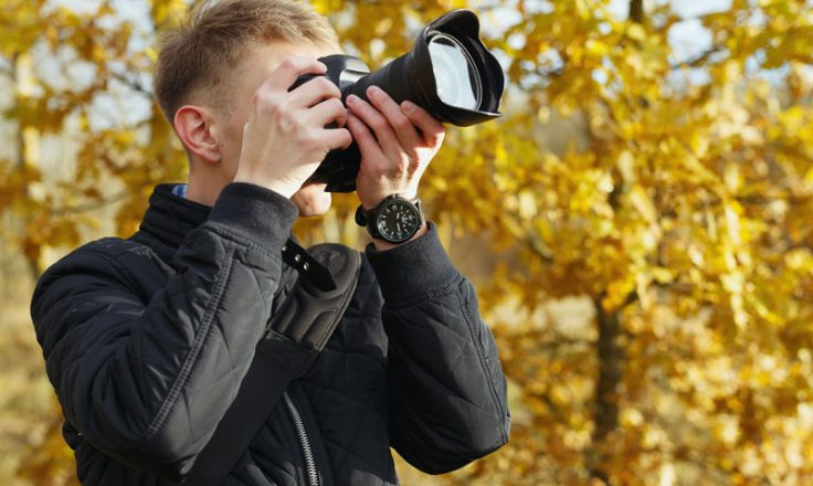man looking through camera wearing a light jacket