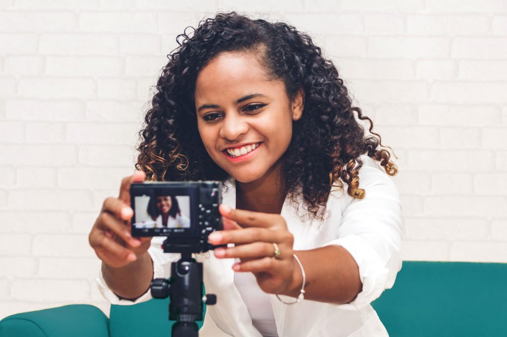woman sitting on couch reaching to push a button on a camera facing her.