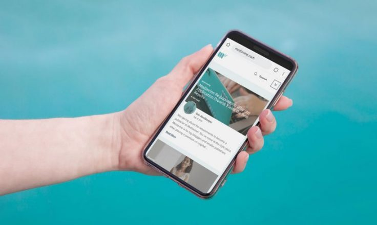 hand holding phone with mediavine website