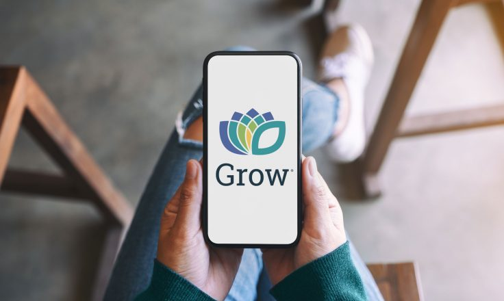 woman wearing jeans and a green sweater holding a photo with the grow.me logo on a phone