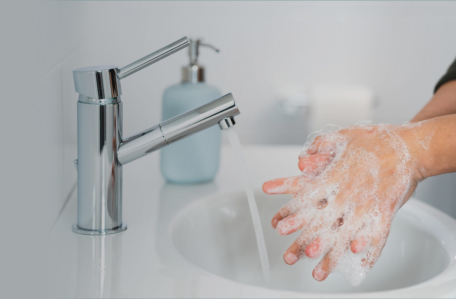 person washing their hands in a gray bathroom