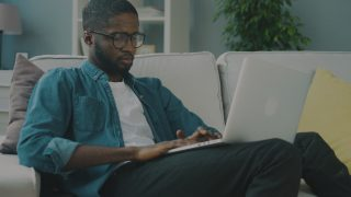 man in denim shirt surfing the web on a white couch