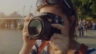 female traveler taking a photo with a dslr camera