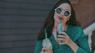 female influencer in teal polka dot shirt drinking tea from a plastic cup