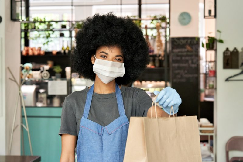 female restaurant worker wearing a mask and handing a brown paper bag to a customer