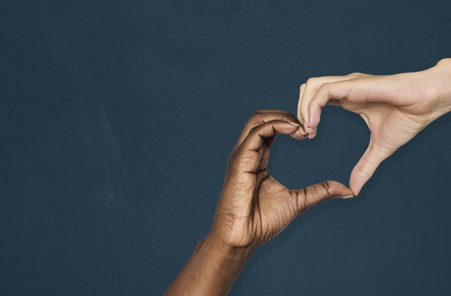 multiracial hands forming a heart shape