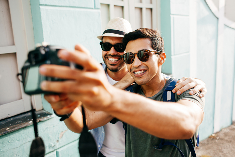 two men posing for a picture holding a camera