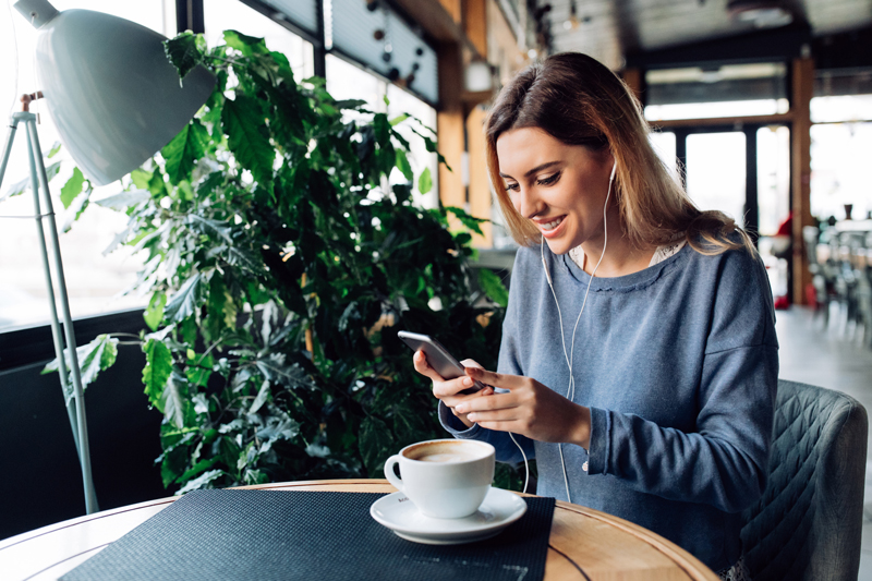 woman in cafe smiling at phone