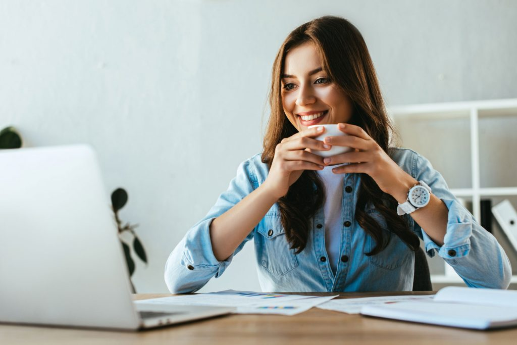 woman smiling at a laptop and holding a cup of coffee