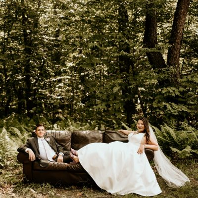 ruthie stewart and husband sitting on a couch in nature on their wedding day