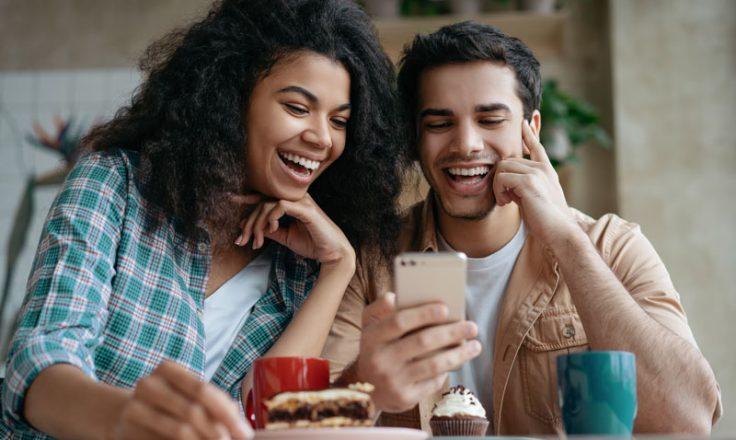 two people smiling at phone while eating baked goods
