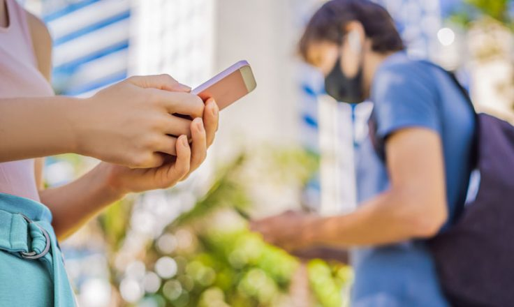 person using phone with another wearing mask in the background